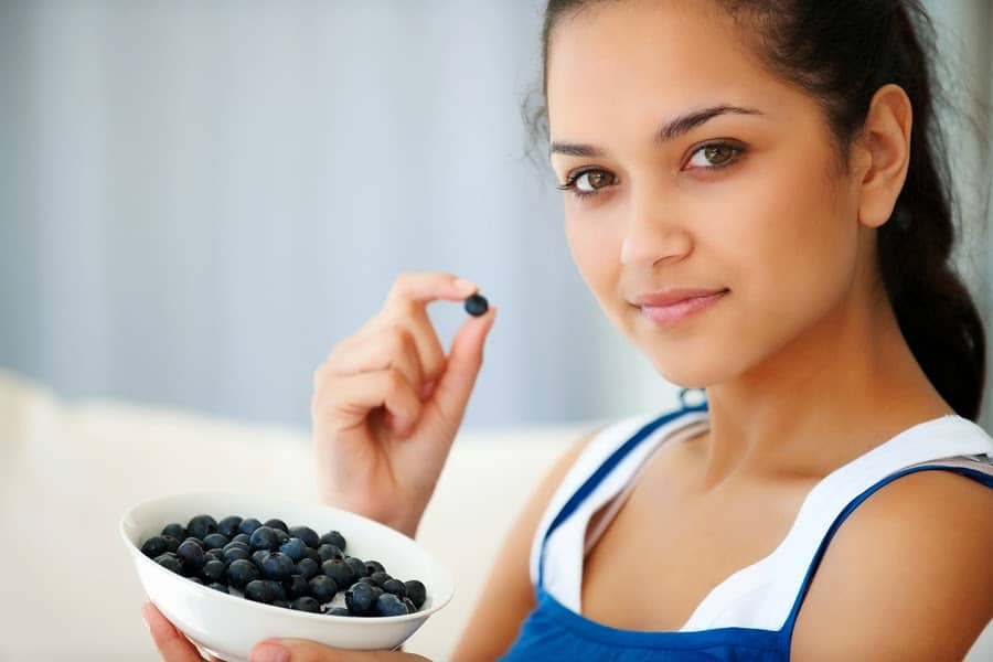 Portrait of sweet young woman eating blackberries at home - Indoors