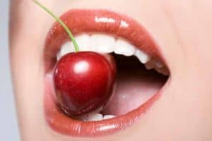 Close-up on woman's mouth with cherry